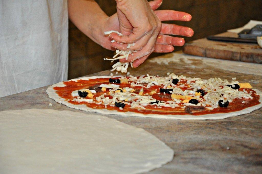 פיזור גבינה על הפיצה - מתכון לפיצה ביתית